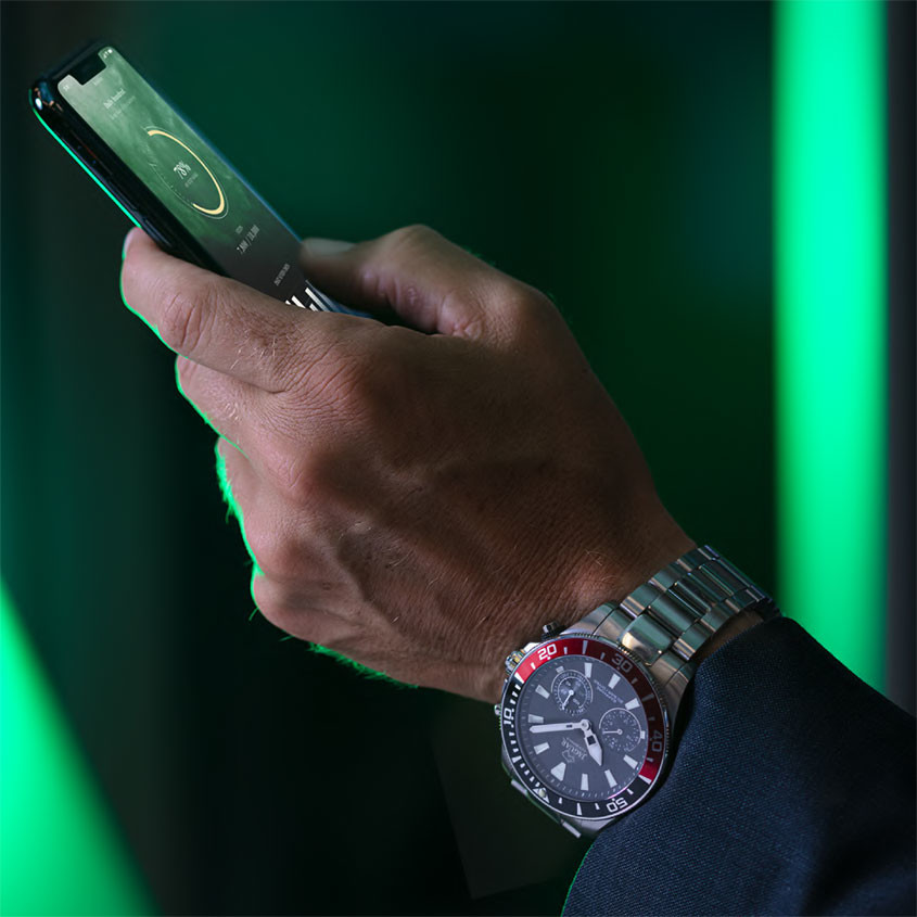 Foto man met telefoon en Jaguar hybrid horloge
