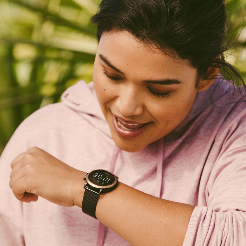 Foto van vrouw die in haar Fossil smartwatch praat